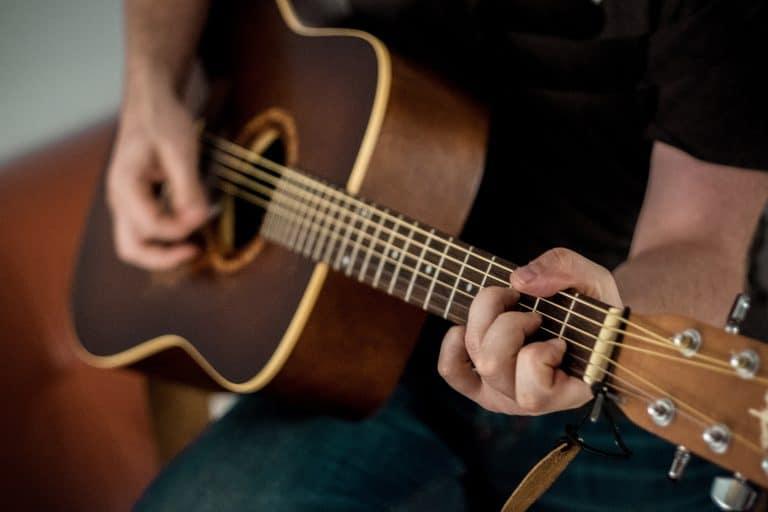 Hombre aprendiendo a tocar guitarra