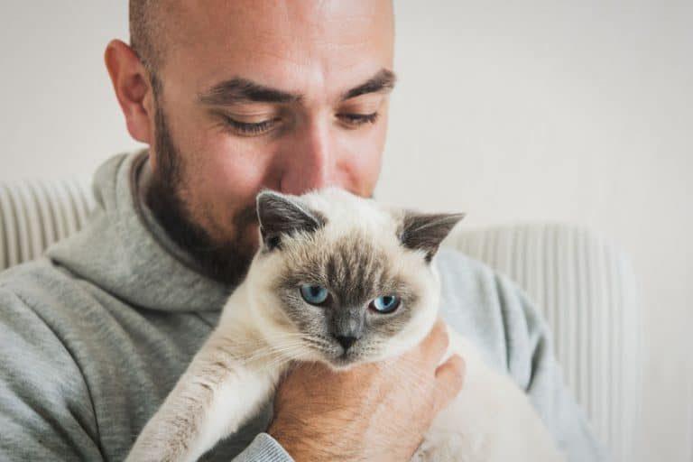 hombre cargando un gato
