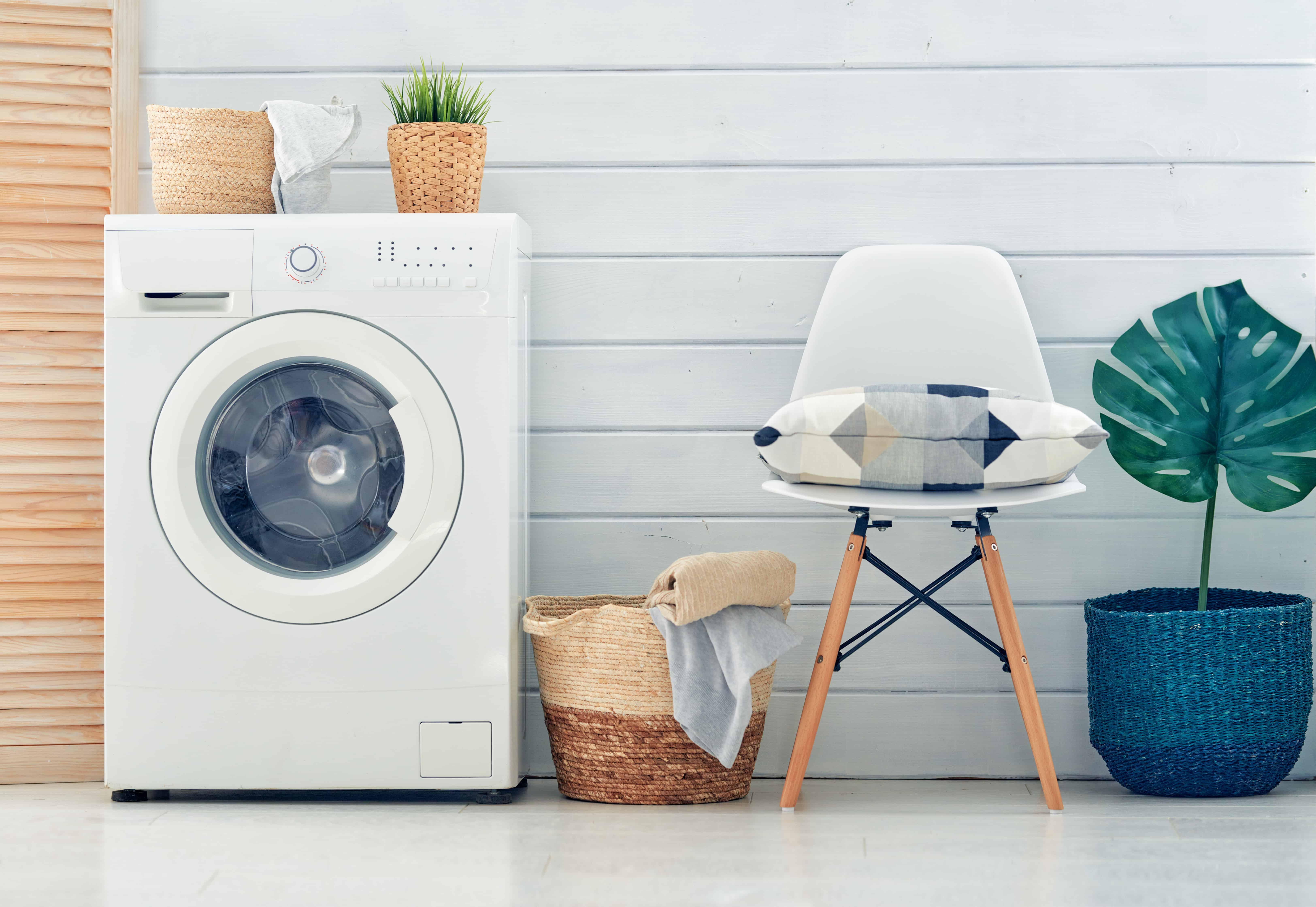 Una lavadora blanca con una silla