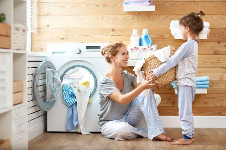 Una madre con su hija poniendo una lavadora