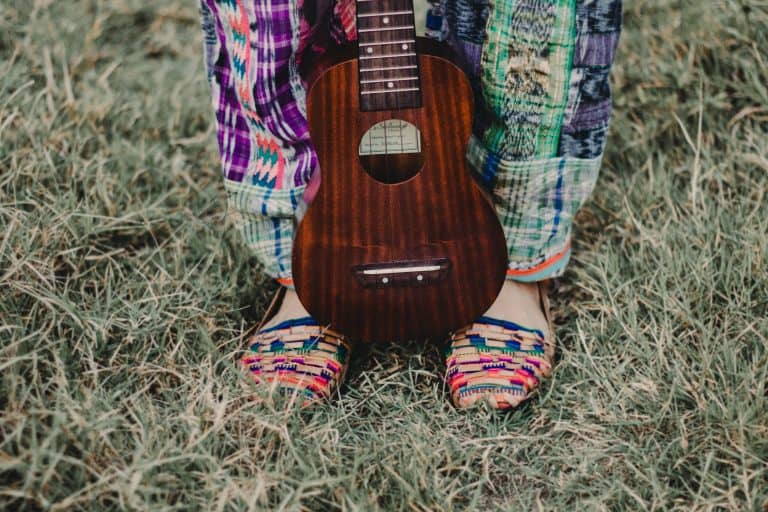 Chica con ukelele sobre sus pies