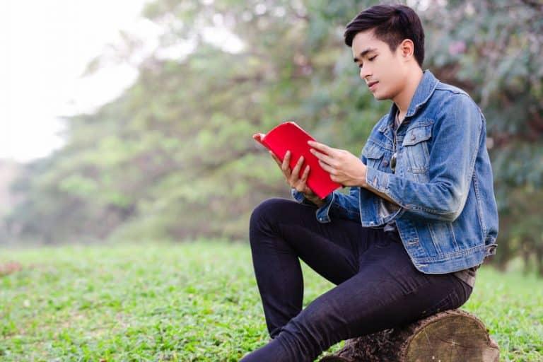 Joven apuesto leyendo en el jardín