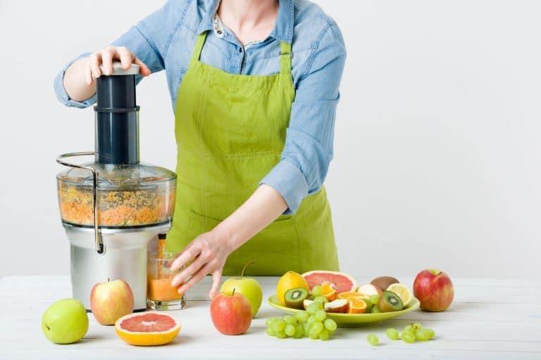 Una mujer haciendo zumo con varias frutas