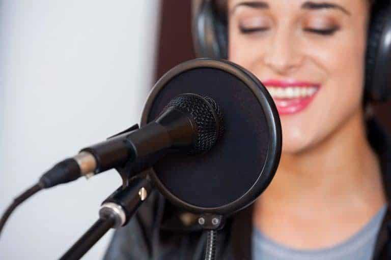 Una chica cantando y usando un micrófono de condensador