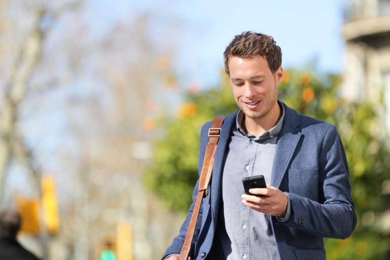 Un chico mirando el móvil por la calle