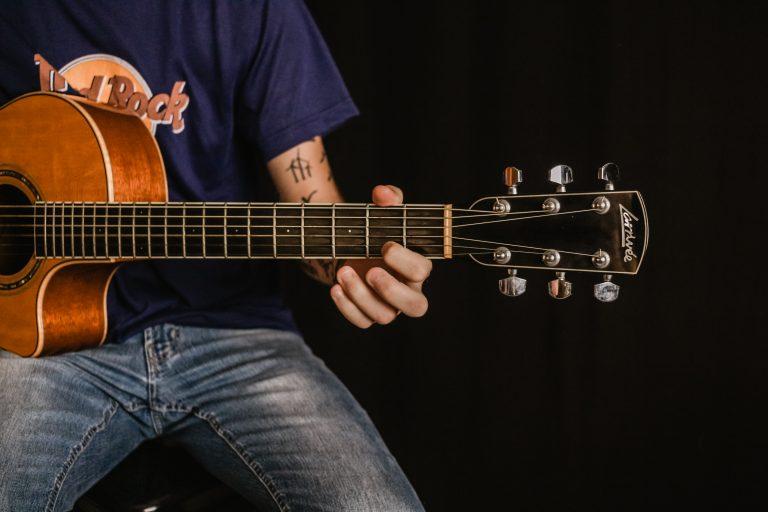 Joven afinando guitarra acústica