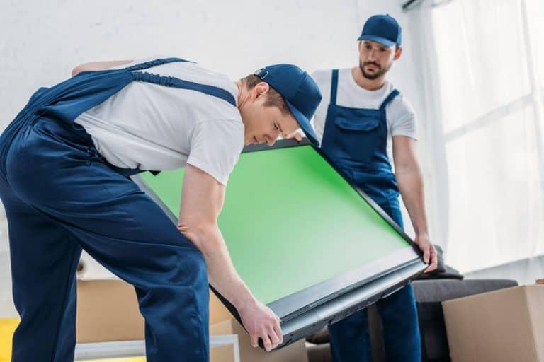 Dos hombres transportando una pantalla verde en una televisión