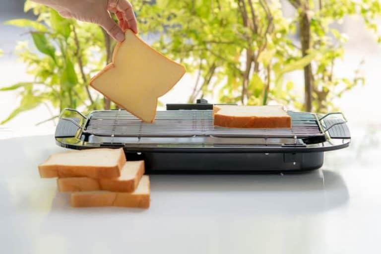 Una persona calentando pan en una parrilla