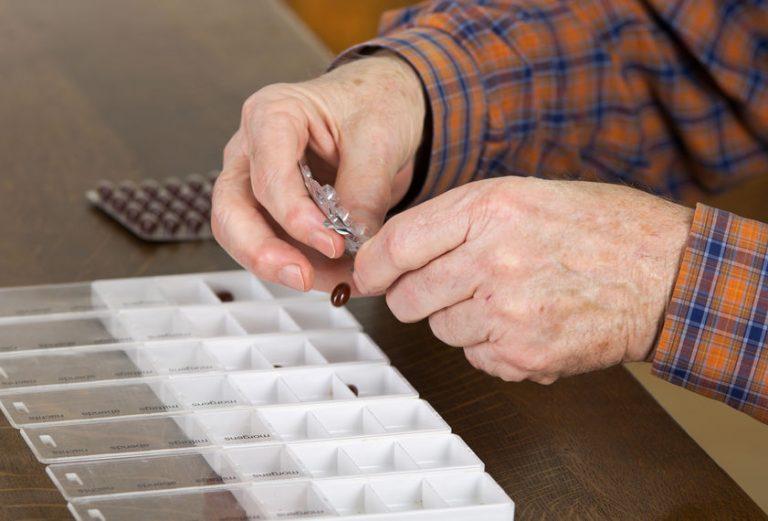 Un hombre mayor organizando su pastillero