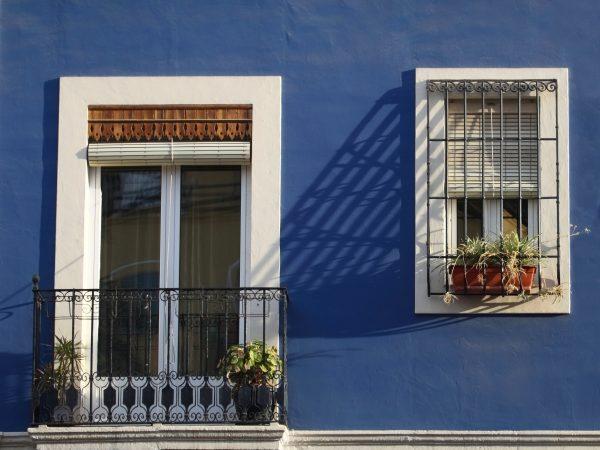 Un balcón y una ventana con persiana alicantina