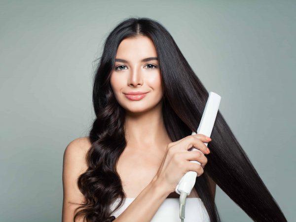 Una chica alisándose el pelo