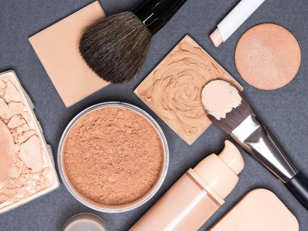 Close-up of concealer pencil, corrector, open liquid foundation bottle and jar of loose powder, crushed compact powder, makeup brushes and cosmetic sponges on gray textured surface