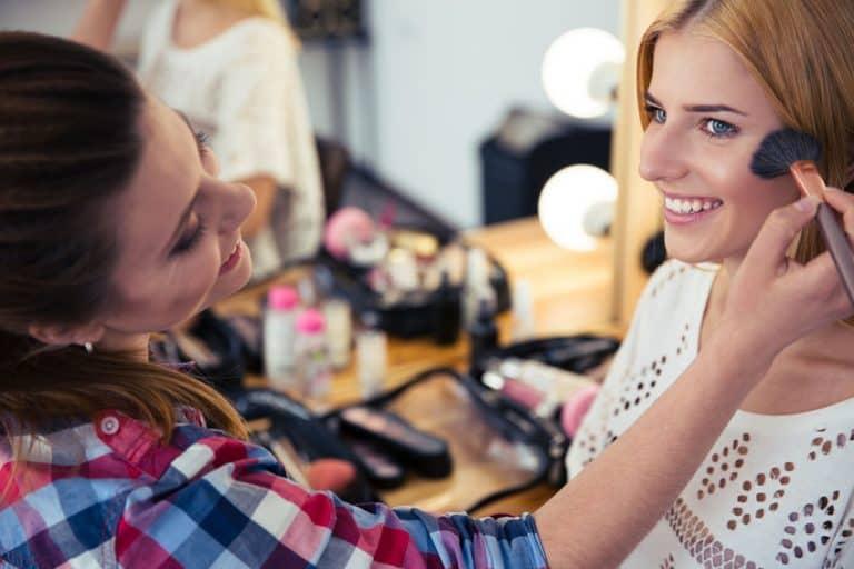 Una maquilladora aplicando polvos a una clienta