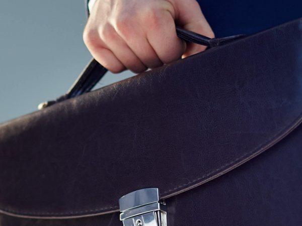 mano sosteniendo maletín