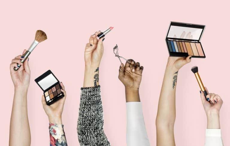 Unas manos sujetando varios accesorios de maquillaje