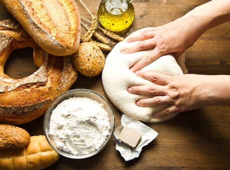 Una persona amasando una masa con pan alrededor