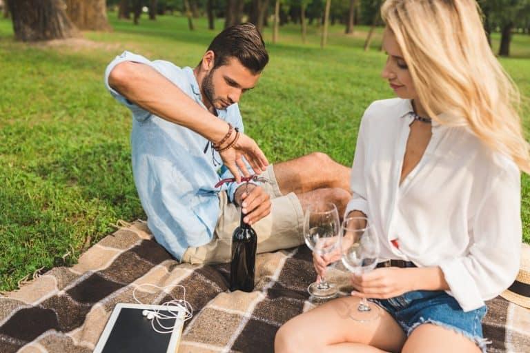 Hombre junto a una mujer abriendo una botella de vino