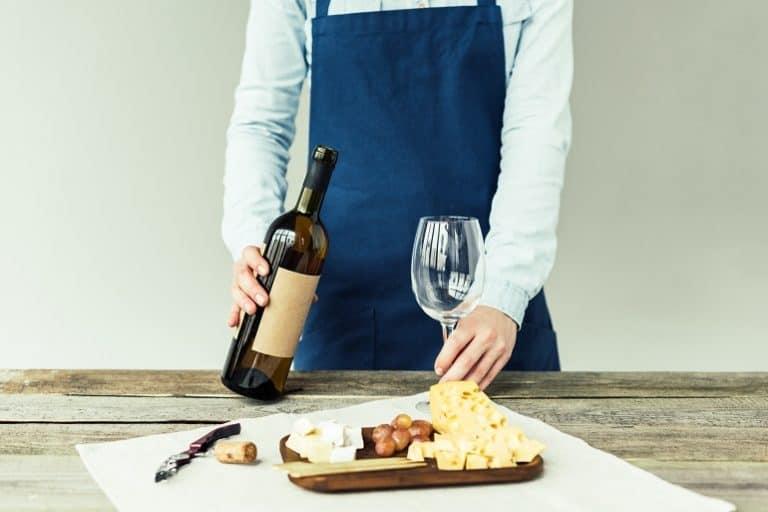 Sommelier con un vino y tabla de quesos