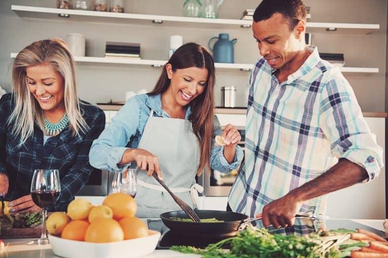 Varios personas cocinando con una sartén