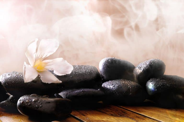 Group of black stones on wood base, steam background. Sauna, therapy, relaxation, and health concept.