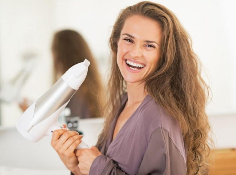 Smiling young woman holding blow dryer