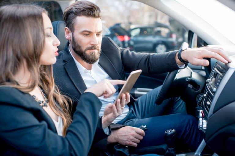 Dos personas en el coche con el móvil