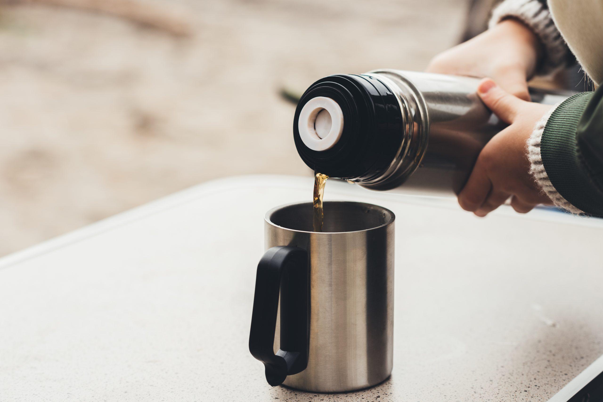 Una persona rellenando un termo para café