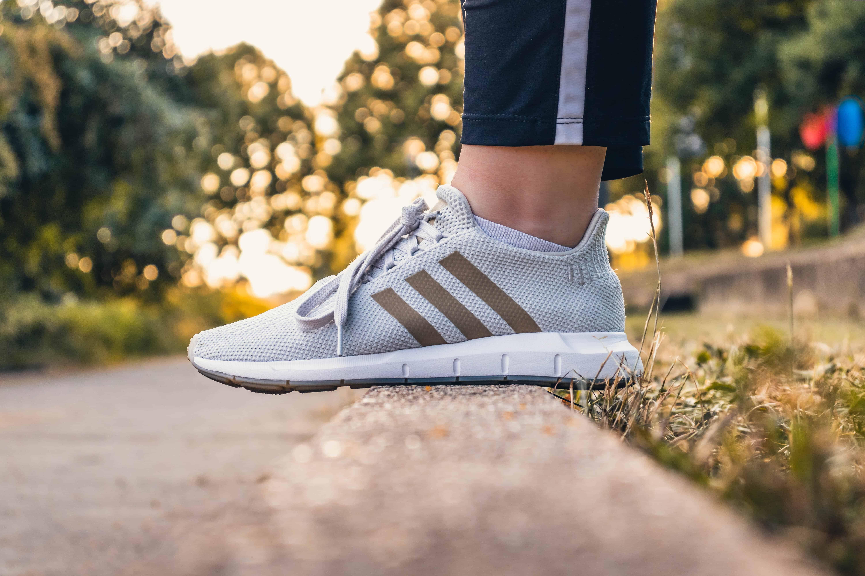 Unos pies con zapatillas adidas en el campo