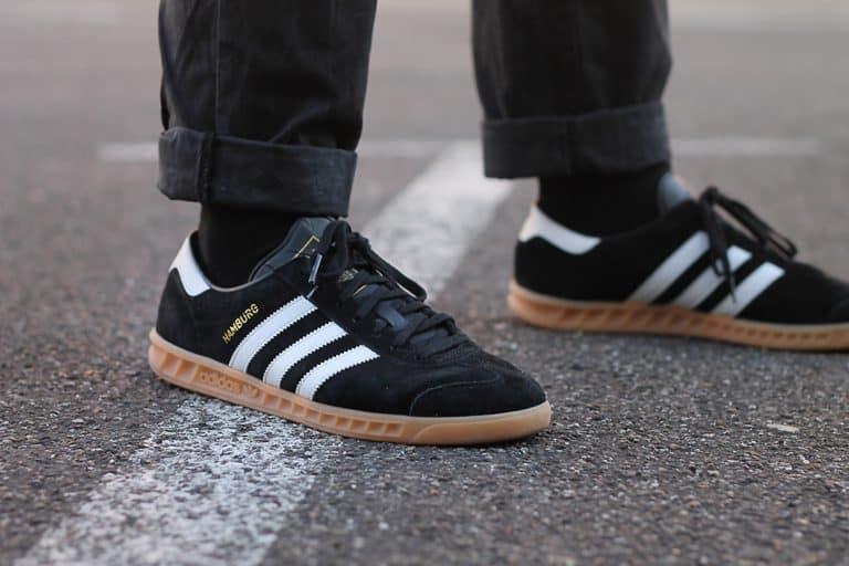 Un chico con unas zapatillas negras adidas