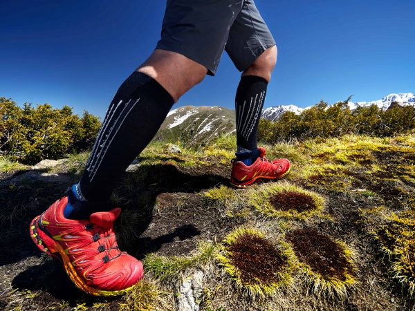 Una persona con unas zapatillas salomon por la montaña