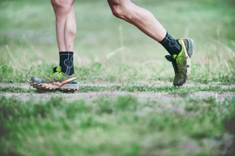 Un hombre corriendo por césped con zapatillas