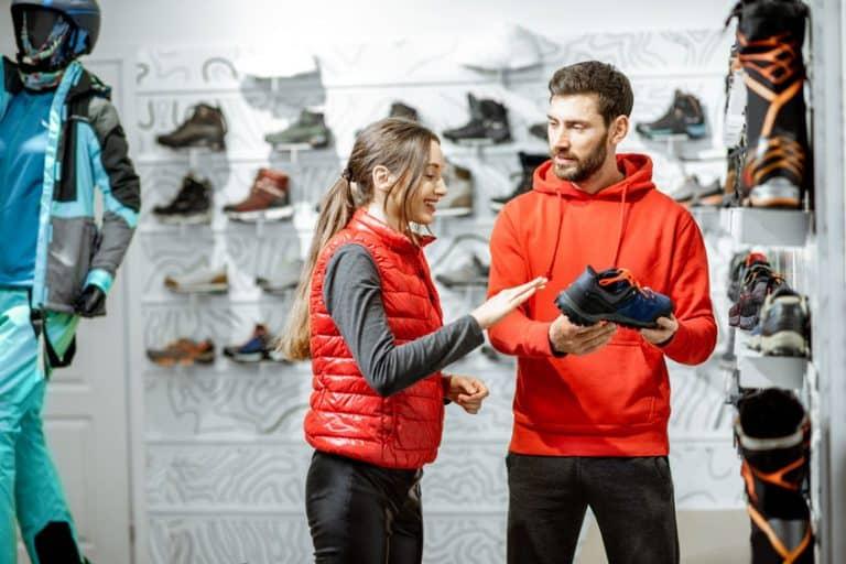 Una vendedora ayudando a un cliente en una tienda deportiva