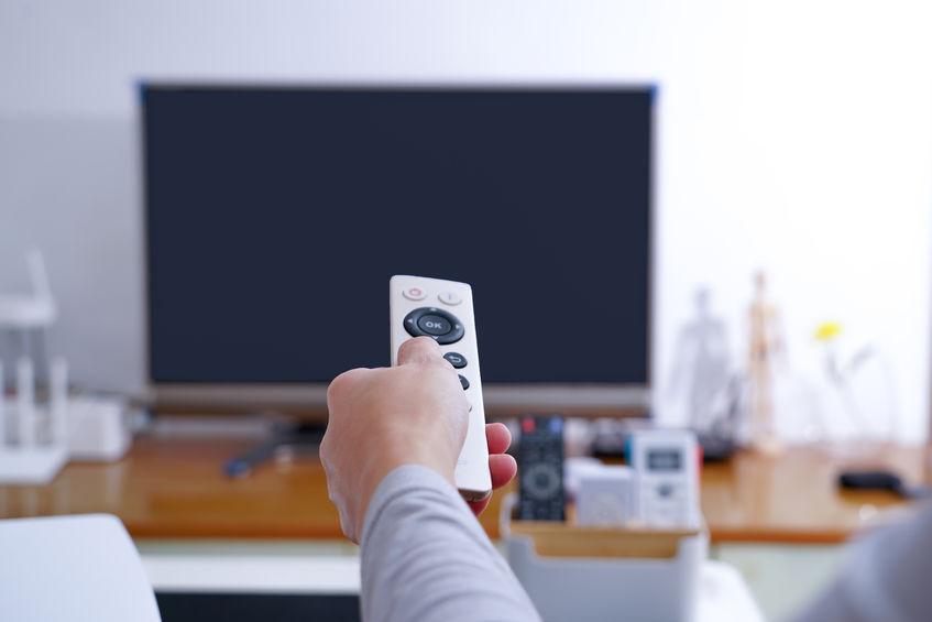 una mano de mujer sostenga el control remoto de la caja de TV en la sala
