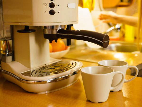 Detailed closeup of coffee maker machine in kitchen. Barista objects, homemade hot drinks concept.