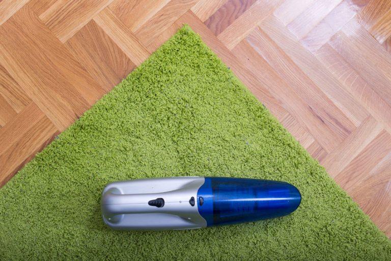 Aspiradora en alfombra verde