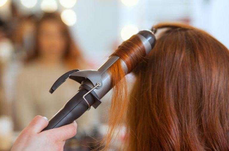 Mujer con rizadora de cabello