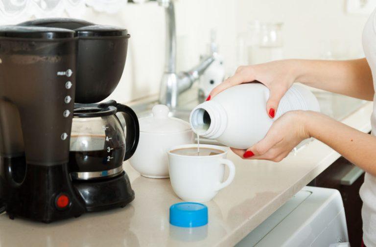 Mujer agregando leche a café