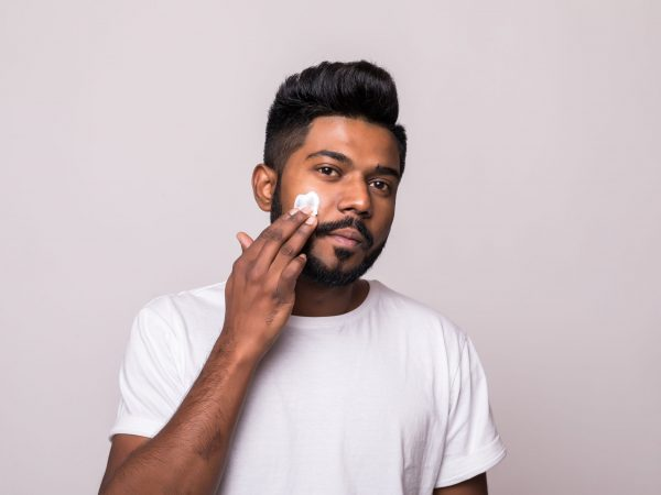 Portrait satisfied young indian man applying facial cream isolated over white background