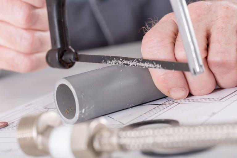 Hombre cortando tubo de plastico