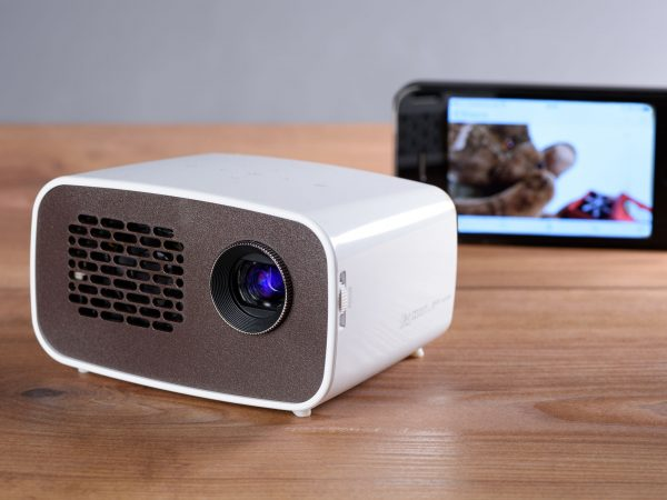 Battery operated mini projector with a smartphone on a desk. The transfer of the image is wireless.