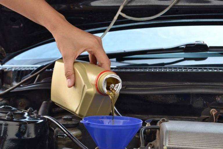Hombre poniendo aceite a su carro