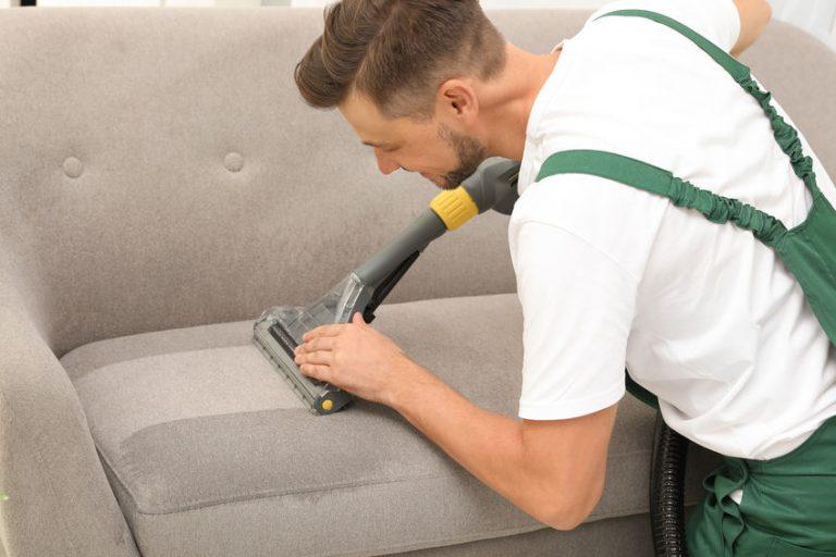 Hombre limpiando sofá
