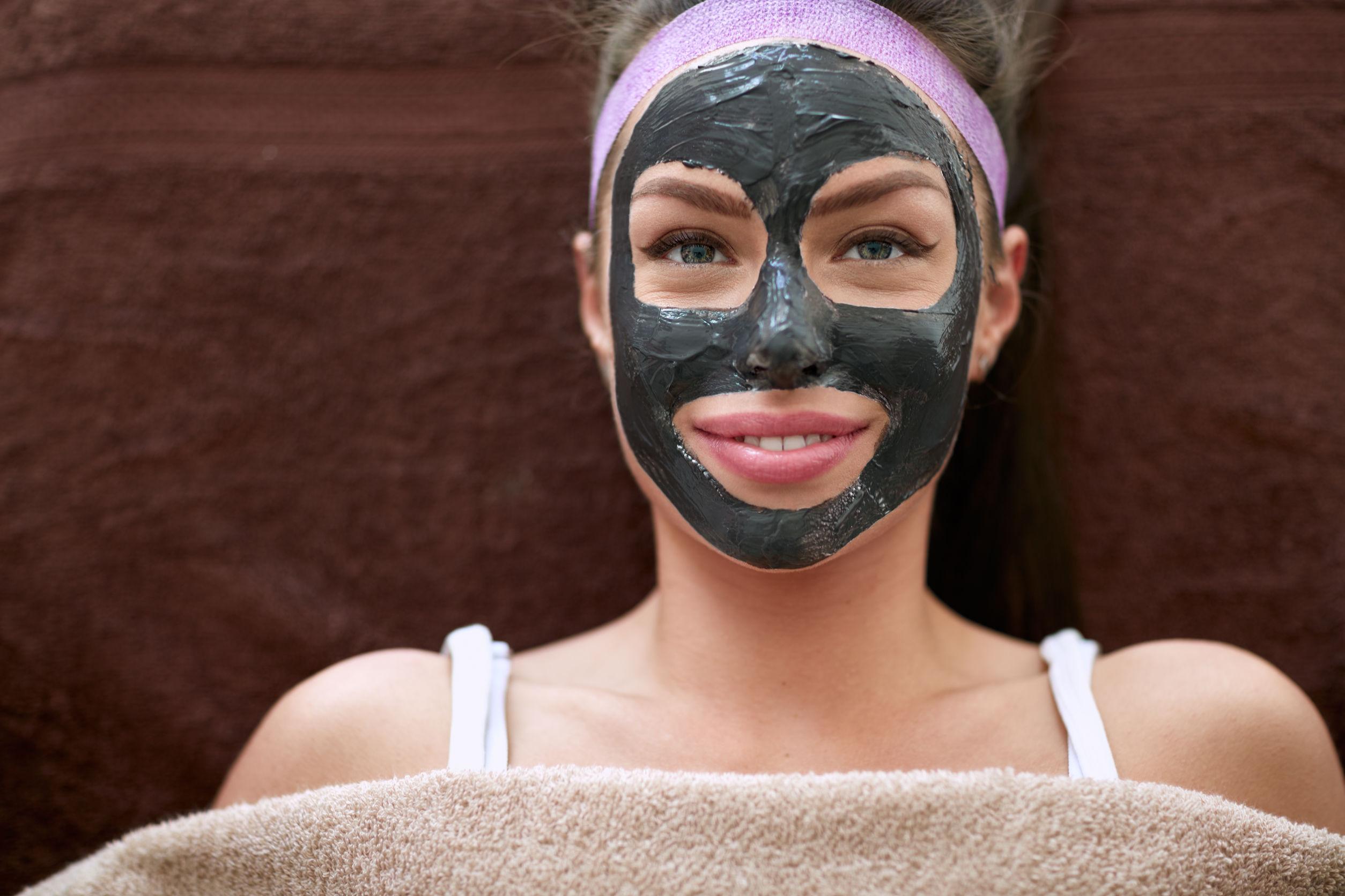 Mujer acostada usando mascarilla negra