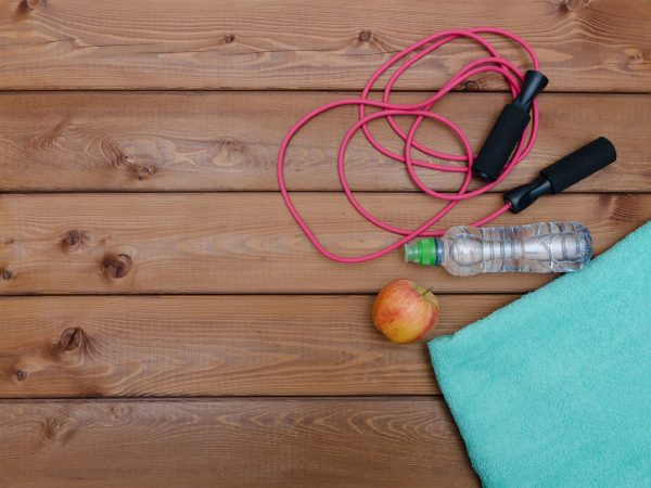 Bottle with towel water and skipping rope on wooden table background. Fitness lifestyle concept.