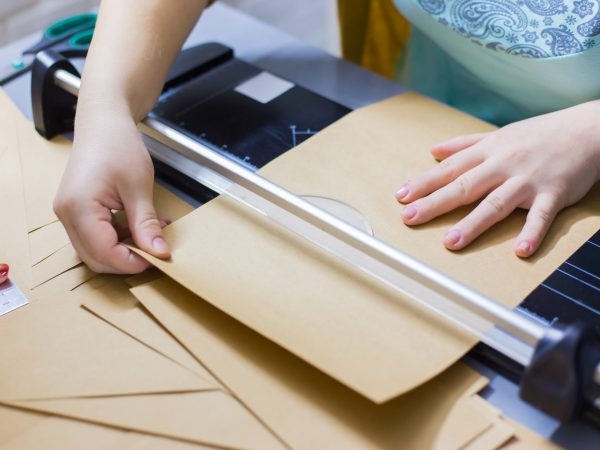 Close up shot – professional woman decorator, designer working with kraft paper and using paper cutter, guillotine at workshop, studio. Crafting work, decoration and art concept