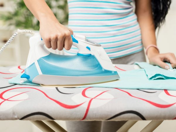 Close-up of a woman hands is ironing clothes.
