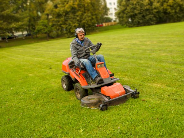 a man driving a lawn mower in a city park