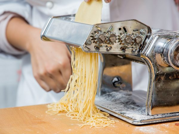 Chief making pasta with a machine