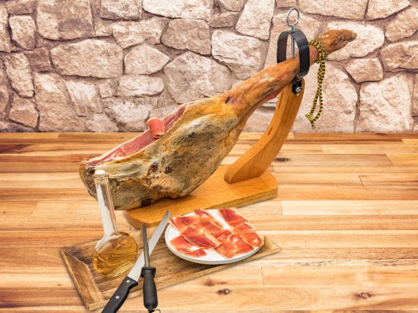 Spanish serrano ham on the leg with wood holder on a table