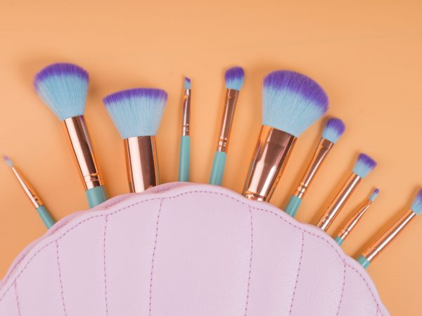 make up brushes isolated on a yellow orange pastel background